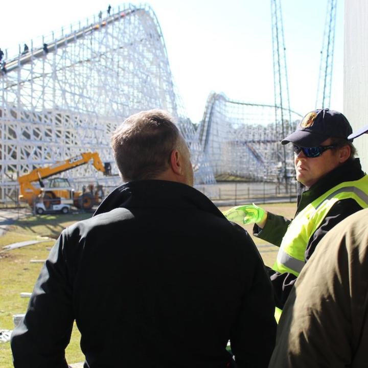 Engineers talking with a roller coaster under construction in the background.
